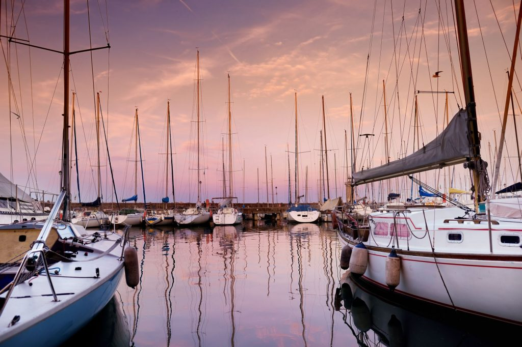 Small yachts in harbor in Desenzano del Garda on beautiful autumn sunset, Lombardy, Italy