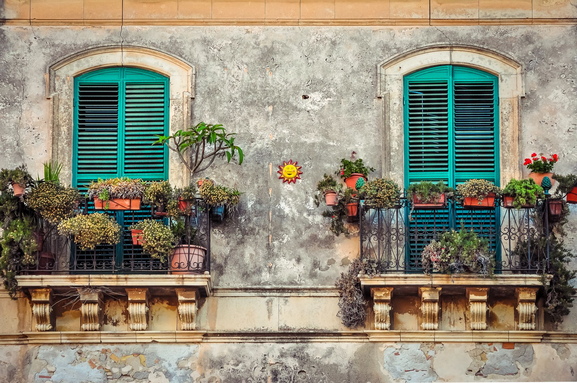 Beautiful vintage balcony with colorful flowers and wooden doors, Mediterranean style